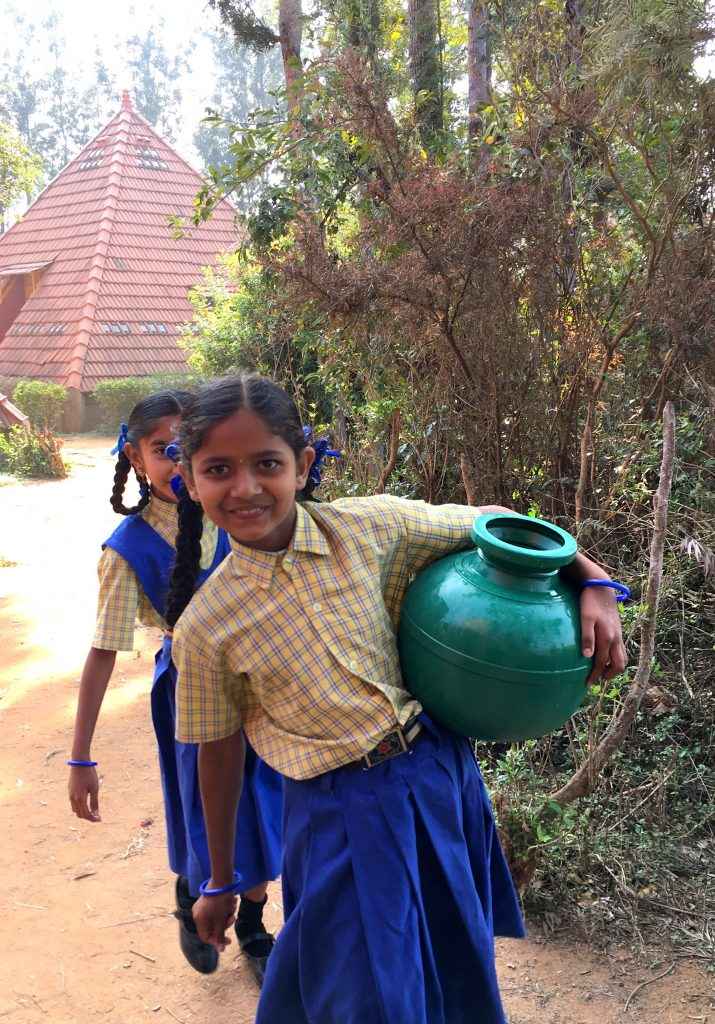 Mentor India - Some of the Paranga girls fetching water to settle the dust on the badminton court